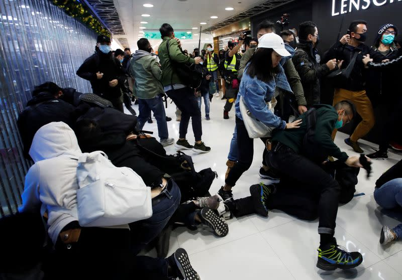 Plain-cloth police officers detain anti-government protesters inside the Sheung Shui shopping mall in Hong Kong