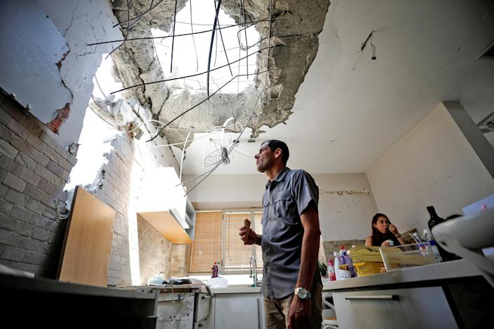 Image: Adi Vaizel, looks at the damage caused to the kitchen of his house after it was hit by a rocket launched from the Gaza Strip earlier this week, in Ashkelon (Amir Cohen / Reuters)