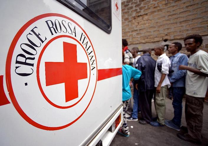 """Migrants queue near a vehicle of the Italian Red Cross outside """"Baobab"""" migration centre next to the Tiburtina train station in Rome on June 14, 2015 (AFP Photo/Filippo Monteforte)"""