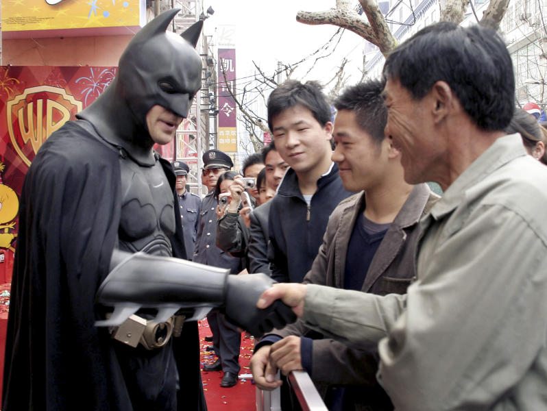 """FILE - In this March 26, 2006 file photo, an actor clad in a Batman costume greets local spectators after the grand opening ceremony of the Warner Bros. Studio Store in Shanghai, China. Hollywood studio Legendary Entertainment which produced """"The Dark Knight"""" from 2008 signed an agreement with the state-owned China Film Group on Thursday, May 30, 2013 in Beijing. (AP Photo/Eugene Hoshiko, File)"""