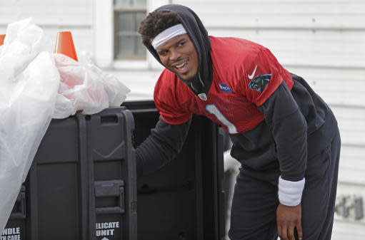 Carolina Panthers' Cam Newton (1) smiles as he changes the music on loudspeakers for practice at the NFL football team's facility in Charlotte, N.C., Tuesday, May 22, 2018. (AP Photo/Chuck Burton)