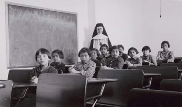 A group of students sit in a residential school classroom in Cross Lake, Manitoba.