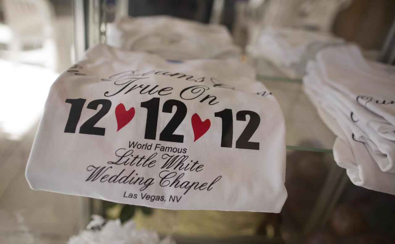 "Tee shirts advertising the 12-12-12 date sit on display at A Little White Wedding Chapel, Tuesday, Dec. 11, 2012, in Las Vegas. These ""once-in-a-century"" wedding dates have become more important each year as people increasingly look outside Vegas for nontraditional weddings. Once known as the wedding capital of the world, Vegas' share of the U.S. wedding market has fallen by a third since 2004. (AP Photo/Julie Jacobson)"