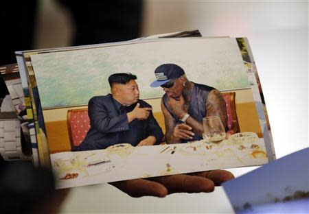 Former basketball star Dennis Rodman of the U.S. shows a picture which he took with North Korean leader Kim Jong-un as he arrives at Beijing Capital International Airport September 7, 2013. REUTERS/Kim Kyung-Hoon