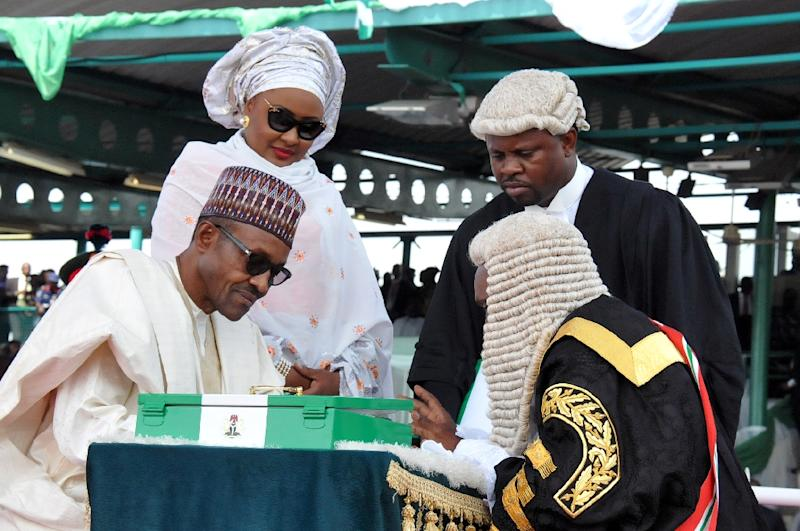 """Nigerian President Mohammadu Buhari (L) once said his wife Aisha (C), """"belongs to my kitchen and my living room and the other room."""" (AFP Photo/STRINGER)"""