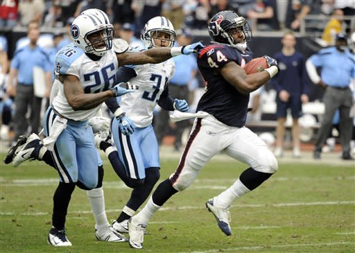 Tennessee Titans strong safety Jordan Babineaux (26) grabs Houston Texans running back Ben Tate (44) as Titans' Cortland Finnegan (31) follows in the third quarter of an NFL football game on Sunday, Jan. 1, 2012, in Houston. (AP Photo/Dave Einsel)