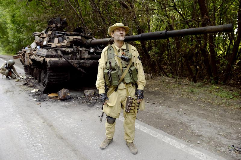A pro-Russia militant stands guard next to a Ukrainian tank that was destroyed by separatists in the eastern city of Donetsk, on July 22, 2014