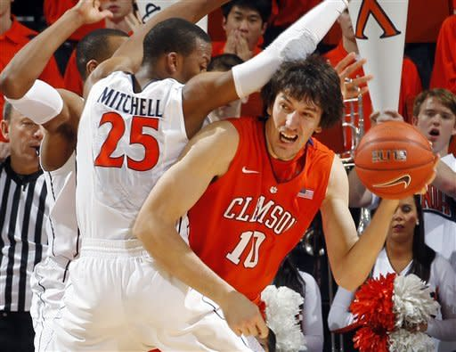 Clemson center Catalin Baciu (10) looks for room around Virginia's Akil Mitchell (25) and Darion Atkins (32) during the second half of an NCAA college basketball game, Tuesday, Jan. 31, 2012, in Charlottesville, Va. Virginia won 65-61. (AP Photo/Andrew Shurtleff)