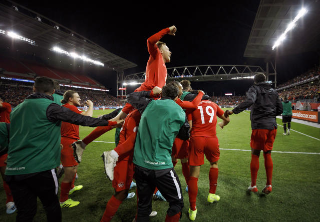 Canada midfielder Scott Arfield, top, and teammates celebrate a goal by forward Lucas Cavallini (19) during the second half of a CONCACAF Nations League soccer match against the United States on Tuesday, Oct. 15, 2019, in Toronto. (Cole Burston/The Canadian Press via AP)