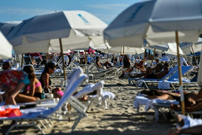People relax on the beach in Miami Beach, Florida -- where massive spring break crowds have caused concern this year