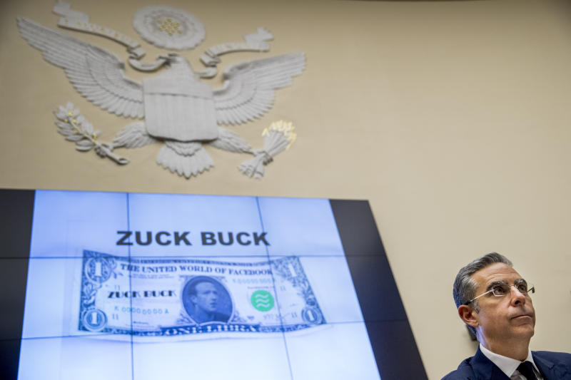 "Facebook CEO Mark Zuckerberg's face is visible on a mock ""Zuck Buck"" depicted on a screen behind David Marcus, CEO of Facebook's Calibra digital wallet service, as he is questioned by Rep. Brad Sherman, D-Calif., during a House Financial Services Committee hearing on Facebook's proposed cryptocurrency on Capitol Hill in Washington, Wednesday, July 17, 2019. (AP Photo/Andrew Harnik)"