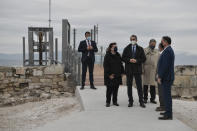 Greek Prime Minister Kyriakos Mitsotakis, third left, Culture Minister Lina Mendoni, second left and President of the Onassis Foundation, Antonis Papadimitriou, fourth left, stand in front of the new elevator at the Acropolis Archaeological site, in Athens, Thursday, Dec. 3, 2020. Acropolis became fully accessible to the disabled and those with mobility issues with a restoration of its terrain and a new elevator. Mitsotakis visited the completed works to mark the international Day for people with disabilities. (Louisa Gouliamaki/Pool via AP)