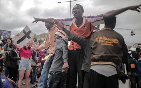 People cheer during a during a march in the streets to demand that President Robert Mugabe resign and step down from power in Harare, Zimbabwe, on November 19, 2017 - Credit: Barcroft Media