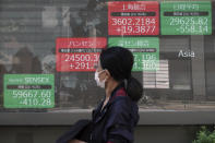 A woman wearing a protective mask walks in front of an electronic stock board showing Japan's Nikkei 225 and other Asian indexes at a securities firm Wednesday, Sept. 29, 2021, in Tokyo. Asian shares fell sharply on Wednesday after a broad slide on Wall Street as investors reacted to a surge in U.S. government bond yields. (AP Photo/Eugene Hoshiko)