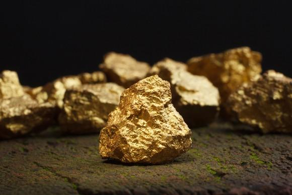 Tiny fragments of gold sitting on a rock.