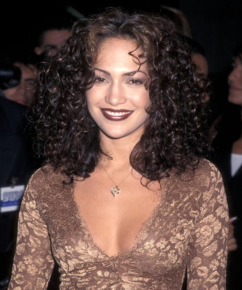 """<h3>1997</h3><br>Though she's usually partial to a soft coral or nude lip color, Lopez rode the brown lipstick train back in the '90s. Her brunette curls and matching lip shade would be equally striking today.<span class=""""copyright"""">Photo: Ron Galella Collection/Getty Images.</span>"""