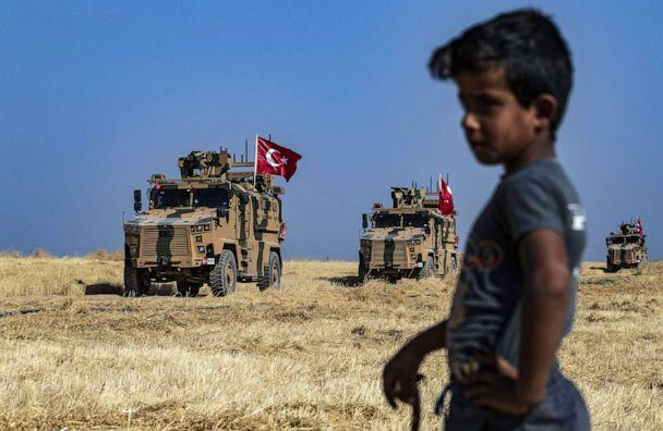PHOTO: A Syrian boy watches as Turkish military vehicles, part of a U.S. military convoy, take part in joint patrol in the Syrian village of al-Hashisha along the border with Turkey, Oct. 4, 2019. (Delil Souleiman/AFP via Getty Images)