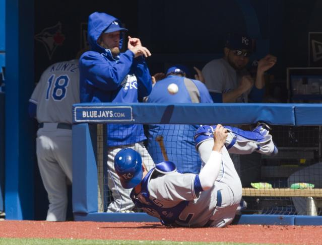 Kansas City Royals catcher Brett Hayes slams into the protective fence in front of his dug out chasing a foul ball off the bat of Toronto Blue Jays Brett Lawrie during the sixth of a baseball game in Toronto, Saturday, May 31, 2014. (AP Photo/The Canadian Press, Fred Thornhill)