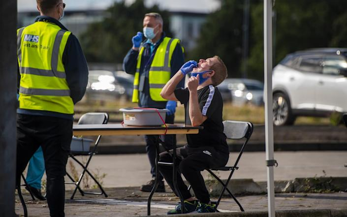 A man swabs his mouth as members of the public attend an NHS Covid Testing facility in Bolton town centre as Coronavirus restrictions are tightened in the area on September 09, 2020 in Bolton, England - Anthony Devlin/Getty Images Europe