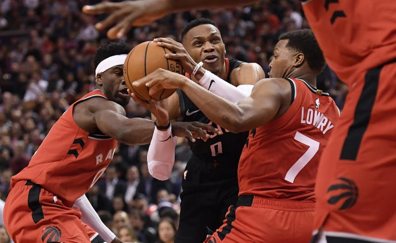Houston Rockets guard Russell Westbrook (0) is fouled as he moves between Toronto Raptors guards Terence Davis, left, and Kyle Lowry (7) during second half NBA action in Toronto on Thursday, Dec.5, 2019. (Nathan Denette/The Canadian Press via AP)