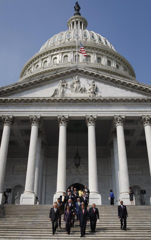 Members of the U.S. Congress gather for a moment of silence in remembrance of lives lost in the 9/11 attacks, on the front steps of the U.S. Capitol in Washington, September 11, 2013. Bagpipes, bells and a reading of the names of the nearly 3,000 people killed when hijacked jetliners crashed into the World Trade Center, the Pentagon and a Pennsylvania field marked the 12th anniversary of the September 11 attacks in 2001. REUTERS/Jonathan Ernst (UNITED STATES - Tags: POLITICS ANNIVERSARY DISASTER)