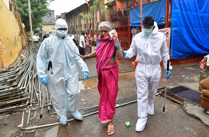 Police officers help the old lady during Covid-19 testing drive at Dharavi, on June 18, 2020 in Mumbai, India. (Photo by Satyabrata Tripathy/Hindustan Times via Getty Images)