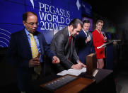 Stakes coordinator Eric Friedman, left, draws a number as assistant racing secretary Michael Costanzo, second from left, pulls out a horse's name during the draw for the Pegasus World Cup Horse Race, Wednesday, Jan. 22, 2020, in Hallandale Beach, Fla. At right are racing analysts Acacia Courtney and Jason Blewitt, second from right, The race will run Saturday, Jan. 25. (AP Photo/Wilfredo Lee)
