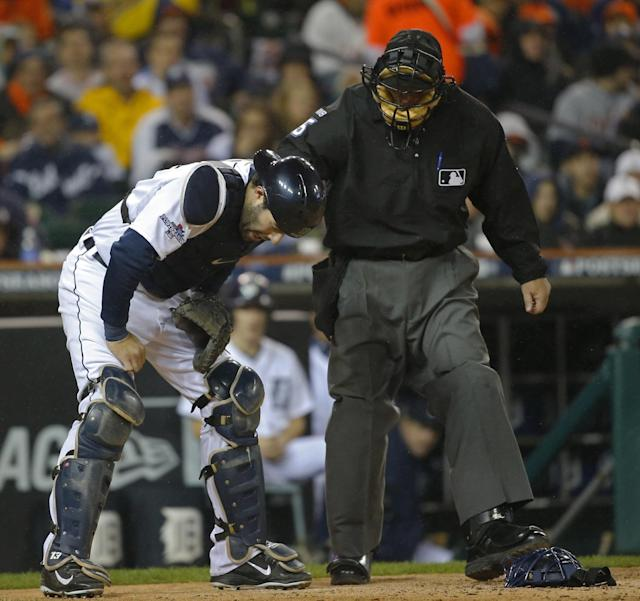 Detroit Tigers catcher Alex Avila is check by umpire Dale Scott after a foul ball in the fourth inning during Game 5 of the American League baseball championship series against the Boston Red Sox, Thursday, Oct. 17, 2013, in Detroit. (AP Photo/Paul Sancya)