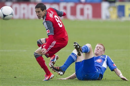 Toronto FC 's Eric Avila, left, is tackled by Montreal Impact's Calum Mallace during second half MLS action in Toronto on Saturday Oct. 20, 2012. (AP Photo/The Canadian Press, Chris Young)