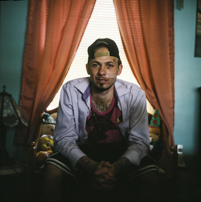 "In this photo made with a medium format film camera, Joshua Messer, 29, sits for a portrait in his aunt's home where he's currently staying, days after he overdosed, in Huntington, W.Va., Tuesday, March 16, 2021. Messer was a high school basketball star, heading to college on a scholarship. He still brags that he was such a star athlete he once met the governor of West Virginia. But addiction took hold, to alcohol and pills. ""I let my family down, now I'm trying to get it back together."" He is covered in prison tattoos, and he likes bright colors and funny socks: he had Bugs Bunny on one foot and Mr. Potato Head on the other. He spent nine years in prison for an addiction-fueled burglary he barely remembers committing. In prison, he got 2020 tattooed on his chest because that was the year he was to be released and supposed to be the year he was to be reborn. He'd gotten a job as a cook at a restaurant and won employee of the month. He planned to save up money and open a landscaping business somewhere, get his own place and his own cat. Messer said the pandemic created a ""circle of nothing,"" that drove him and other people he knows to using more drugs. He said he took heroin eight months ago for the first time and thought he could do it just once, but he woke up the next morning needing more. ""I look at some people and it's sad how they look,"" he said. ""I'm starting to look like that. It's sad. I'm not better than other people. But I'm better than letting something take control of my life. I feel like I should be better than this."" (AP Photo/David Goldman)"