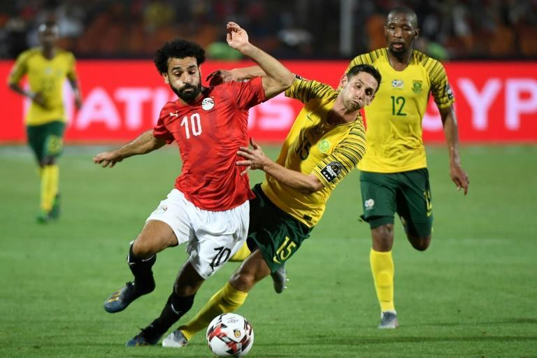 Egypt star Mohamed Salah (L) holds off South African Dean Furman during a 2019 Africa Cup of Nations (CAN) last 16 clash in Cairo.