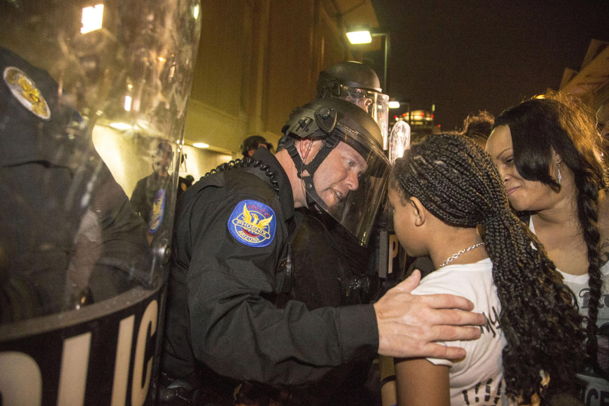 In this Monday, Dec. 8, 2014 photo, a Phoenix police officer in riot gear talks with Aiyana Rains, 9, the daughter of Rumain Brisbon, as she participates with hundreds of protesters headed towards police headquarters to demand transparency in the case that left her father dead following a confrontation with a police officer on Dec. 2. Grasping her hand, the officer said,