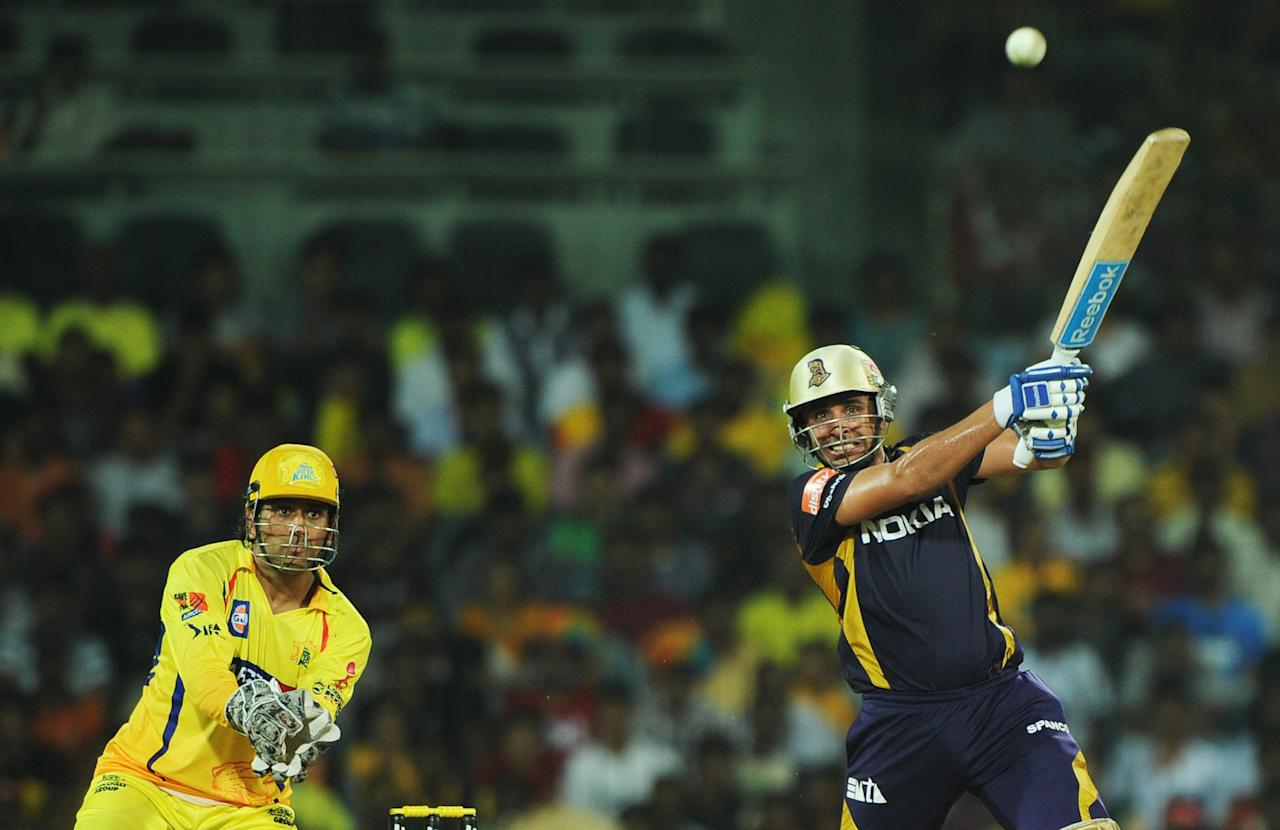 Kolkata Knight Riders batsman Manvinder Bisla (R) is watched by Chennai Super Kings captain Mahendra Singh Dhoni (L) as he plays a shot during the IPL Twenty20 cricket final match between Chennai Super Kings and Kolkata Knight Riders at the M.A. Chidambaram Stadium in Chennai on May 27, 2012.  RESTRICTED TO EDITORIAL USE. MOBILE USE WITHIN NEWS PACKAGE.  AFP PHOTO/Dibyangshu SARKAR