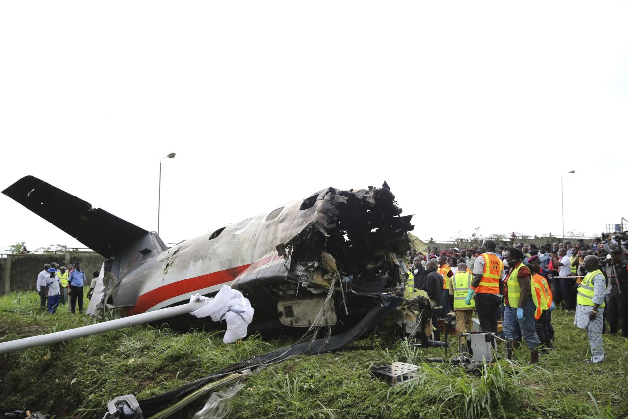 Rescue workers stand near the tail of a plane at the site of a plane crash near the Lagos international airport October 3, 2013. Fifteen people were killed when an Embraer passenger plane crashed shortly after take-off just outside Lagos airport's domestic terminal on Thursday, Nigerian authorities said. REUTERS/Akitnunde Akinleye (NIGERIA - Tags: DISASTER SOCIETY TPX IMAGES OF THE DAY)