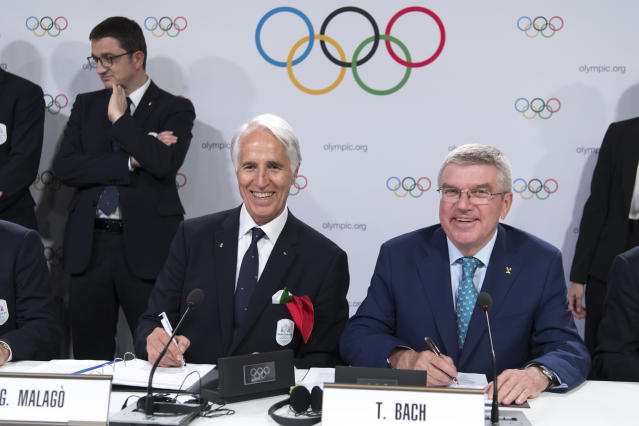 International Olympic Committee (IOC) president Thomas Bach, right, from Germany and Italy's National Olympic Committee (CONI) president Giovanni Malago, left, pose signing documents with Italian delegation after Milan-Cortina won the bid to host the 2026 Winter Olympic Games, during the first day of the 134th Session of the International Olympic Committee (IOC), at the SwissTech Convention Centre, in Lausanne, Switzerland, Monday, June 24, 2019. Italy will host the 2026 Olympics in Milan and Cortina d'Ampezzo, taking the Winter Games to the Alpine country for the second time in 20 years. (Laurent Gillieron/Keystone via AP)