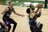 Milwaukee Bucks' Khris Middleton drives to the basket against Philadelphia 76ers' Tobias Harris and George Hill during the first half of an NBA basketball game Thursday, April 22, 2021, in Milwaukee. (AP Photo/Aaron Gash)