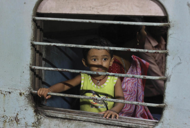 In this Saturday, Aug. 18, 2012 photo, a child from India's northeastern state looks from a train compartment as he and his family try to return to their home in Ahmadabad, India. Indian Home Secretary R.K. Singh has accused websites in Pakistan of spreading false rumors that caused thousands of people from India's remote northeast to panic and flee the southern city of Bangalore. They feared they would be attacked in retaliation for ethnic violence in their home state. (AP Photo/Ajit Solanki)