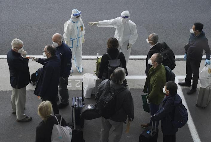 A group of people with suitcases stand in front of two people in head-to-toe protective gear.