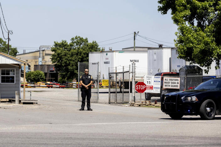 A police officer stands at the entrance to a Mueller Co. fire hydrant plant where police said multiple people were shot to death and others were wounded in Albertville, Ala., on Tuesday, June 15, 2021. (AP Photo/Vasha Hunt)