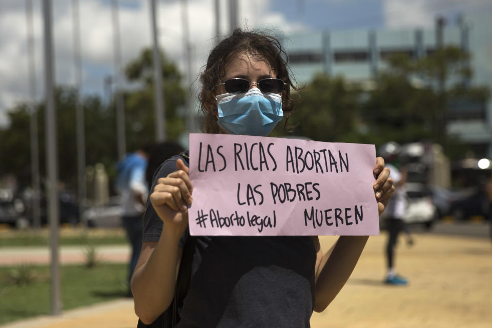 """A woman holds a sign reading """"the rich abort, the poor die"""" during a demonstration for the decriminalization of abortion in three circumstances - when the life of the pregnant woman is in danger, when the pregnancy is the product of rape or when the pregnancy is unviable - in Santo Domingo, on August 25, 2020. (Photo by Erika SANTELICES / AFP) (Photo by ERIKA SANTELICES/afp/AFP via Getty Images)"""