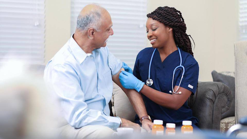 Senior adult, male patient receives vaccine or medicine from his African descent, home healthcare nurse in nursing home or home setting.