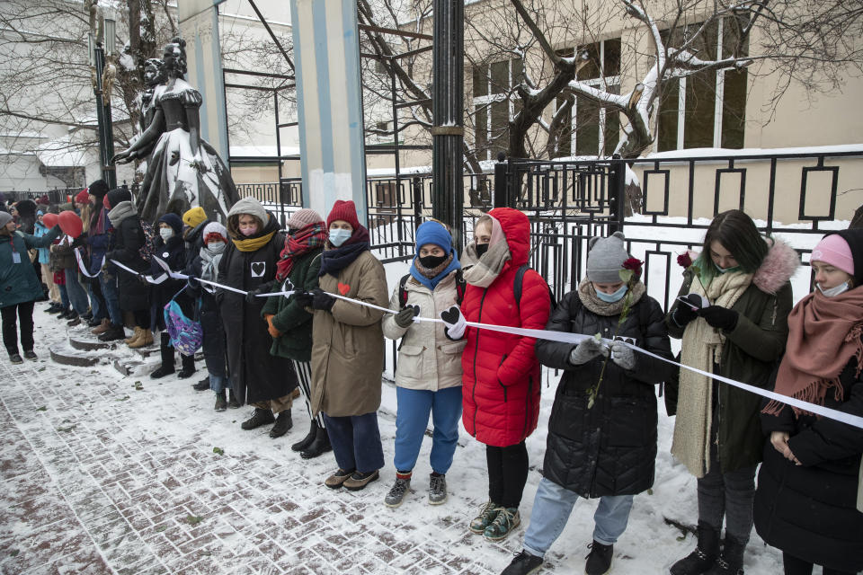 Women hold a white ribbon as they stand in a line during a rally in support of jailed opposition leader Alexei Navalny, and his wife Yulia Navalnaya in Moscow, Russia, Sunday, Feb. 14, 2021. The weekend protests in scores of cities last month over Navalny's detention represented the largest outpouring of popular discontent in years and appeared to have rattled the Kremlin. (AP Photo/Pavel Golovkin)