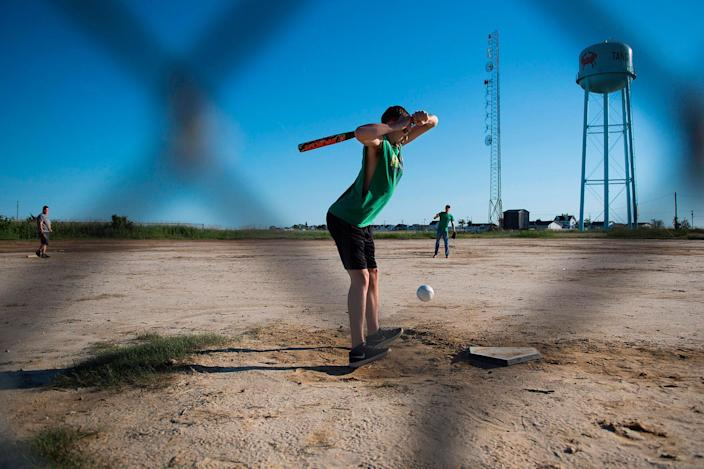 <p>Teenage boys play baseball on a dirt lot in Tangier, Virginia, May 16, 2017, where climate change and rising sea levels threaten the inhabitants of the slowly sinking island.<br> (Jim Watson/AFP/Getty Images) </p>