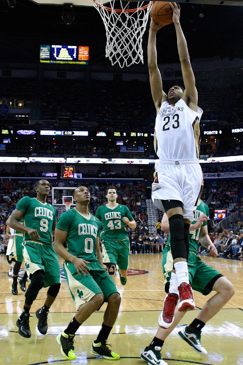 New Orleans Pelicans forward Anthony Davis (23) shoots past Boston Celtics guard Rajon Rondo (9), guard Avery Bradley (0), center Kris Humphries (43) and center Kelly Olynyk, right, during the first half of an NBA basketball game in New Orleans, Sunday, March 16, 2014. (AP Photo/Jonathan Bachman)