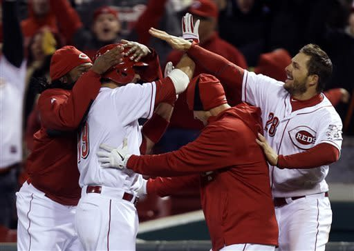 Cincinnati Reds' Joey Votto (19) is mobbed by his teammates after he drove in the winning run ing the bottom of the ninth inning of a baseball game against the Los Angeles Angels, Wednesday, April 3, 2013, in Cincinnati. Cincinnati won 5-4. (AP Photo/Al Behrman)