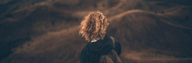 back of a girl with curly hair and a backpack looking out into the vast mountains