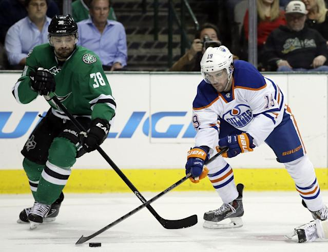 Dallas Stars' Vernon Fiddler (38) and Edmonton Oilers' Justin Schultz (19) compete for a loose puck in the first period of an NHL Hockey game, Tuesday, Jan. 14, 2014, in Dallas. (AP Photo/Tony Gutierrez)