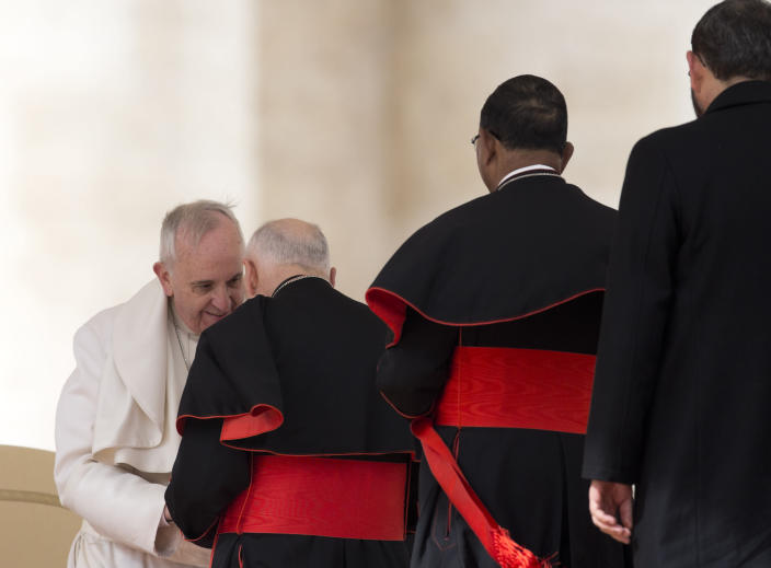 FILE - In this Feb. 19, 2014 file photo, Pope Francis greets U.S. Cardinal Theodore Edgar McCarrick in St. Peter's Square at the Vatican, at the end of his general audience. On Tuesday, Nov. 10, 2020, the Vatican is taking the extraordinary step of publishing its two-year investigation into the disgraced ex-Cardinal McCarrick, who was defrocked in 2019 after the Vatican determined that years of rumors that he was a sexual predator were true. (AP Photo/Alessandra Tarantino, File)