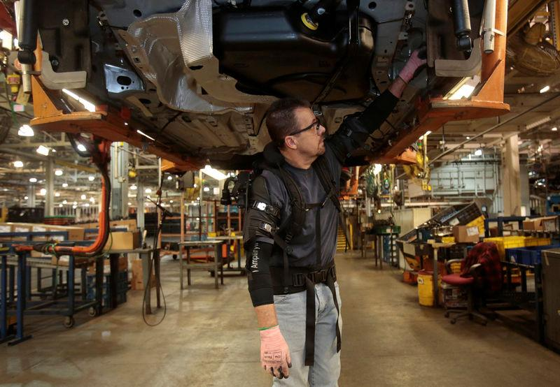 Ford Motor Co assembly worker Paul Collins wears a EksoVest as he works on the assembly line producing the Ford Focus and C-max at Wayne Assembly plant