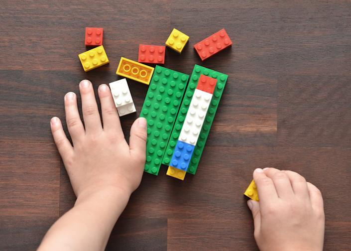 Vancouver, B.C., Canada -- May 28, 2015:Closeup of a 5 year old boy playing with Lego building blocks on a wood table.  Lego is a popular toy brand that is available worldwide.